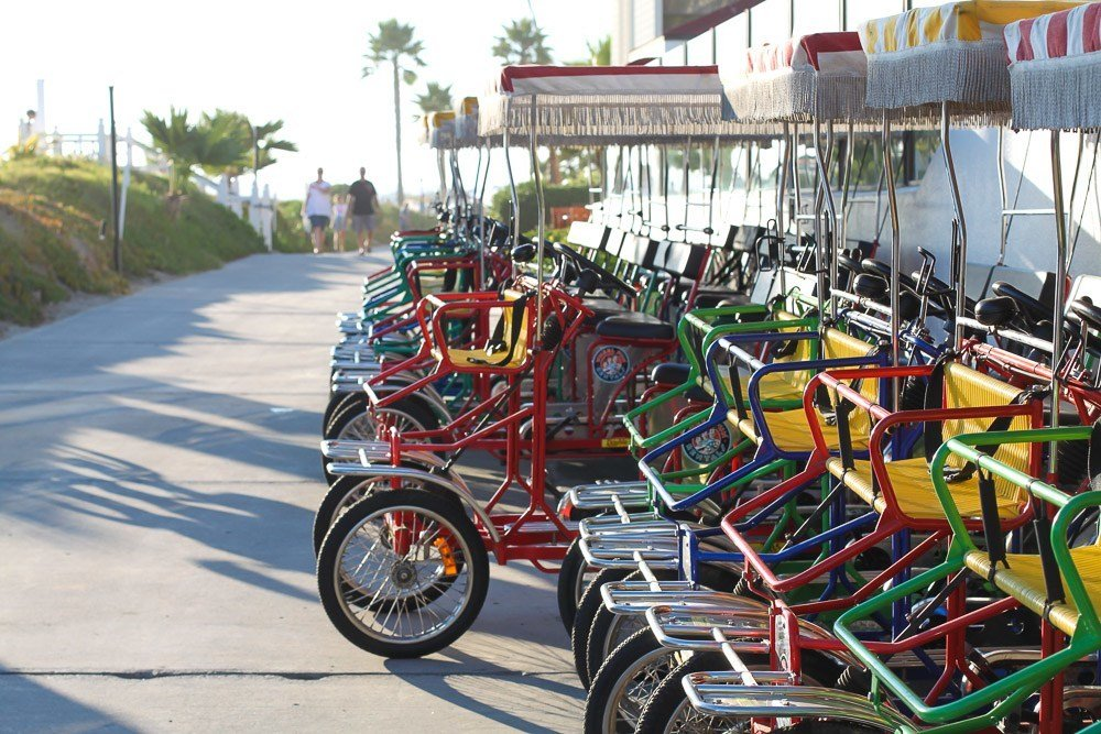 Hotel Del Coronado bike rentals with surreys lined up near the boardwalk.