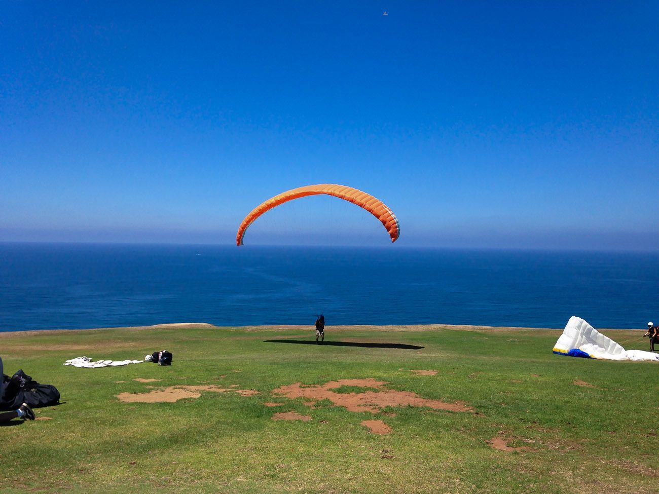 A glider with an orange parachute prepares to run off the cliff to take-off, one of the coolest outdoor activities San Diego has to offer.