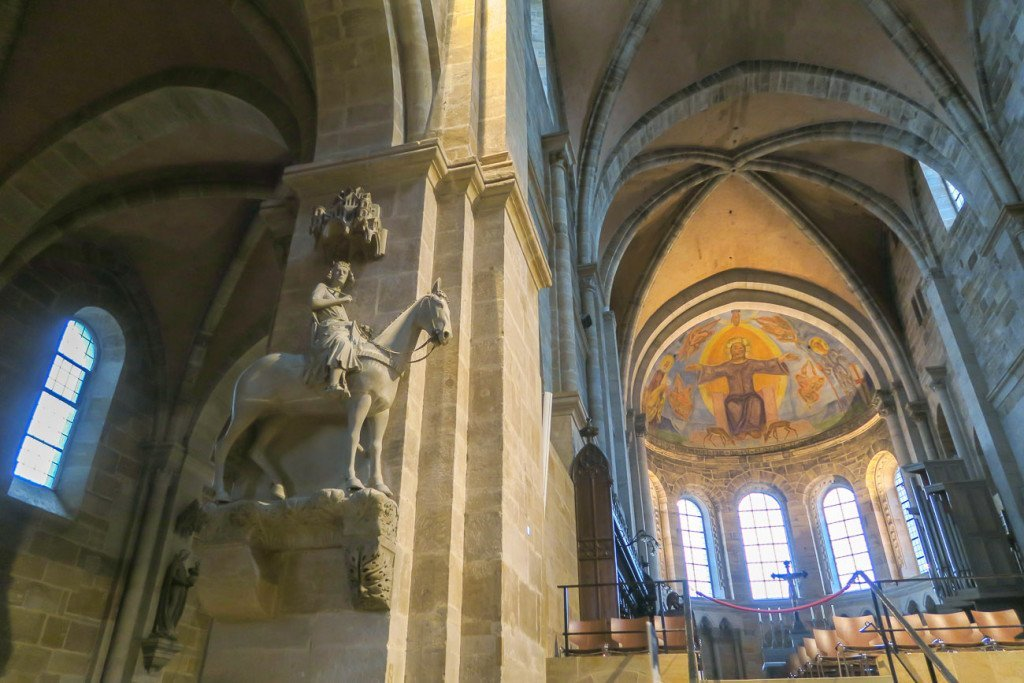 A horseman statue with domed ceiling in the background inside Bamberg Cathedreal