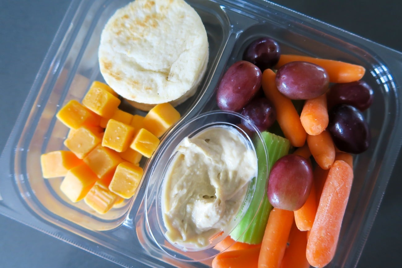 Healthy convenience store snacks: cheese, grapes, hummus and veggies.