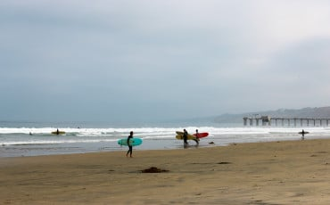 Surfers on La Jolla Shores beach in San Diego