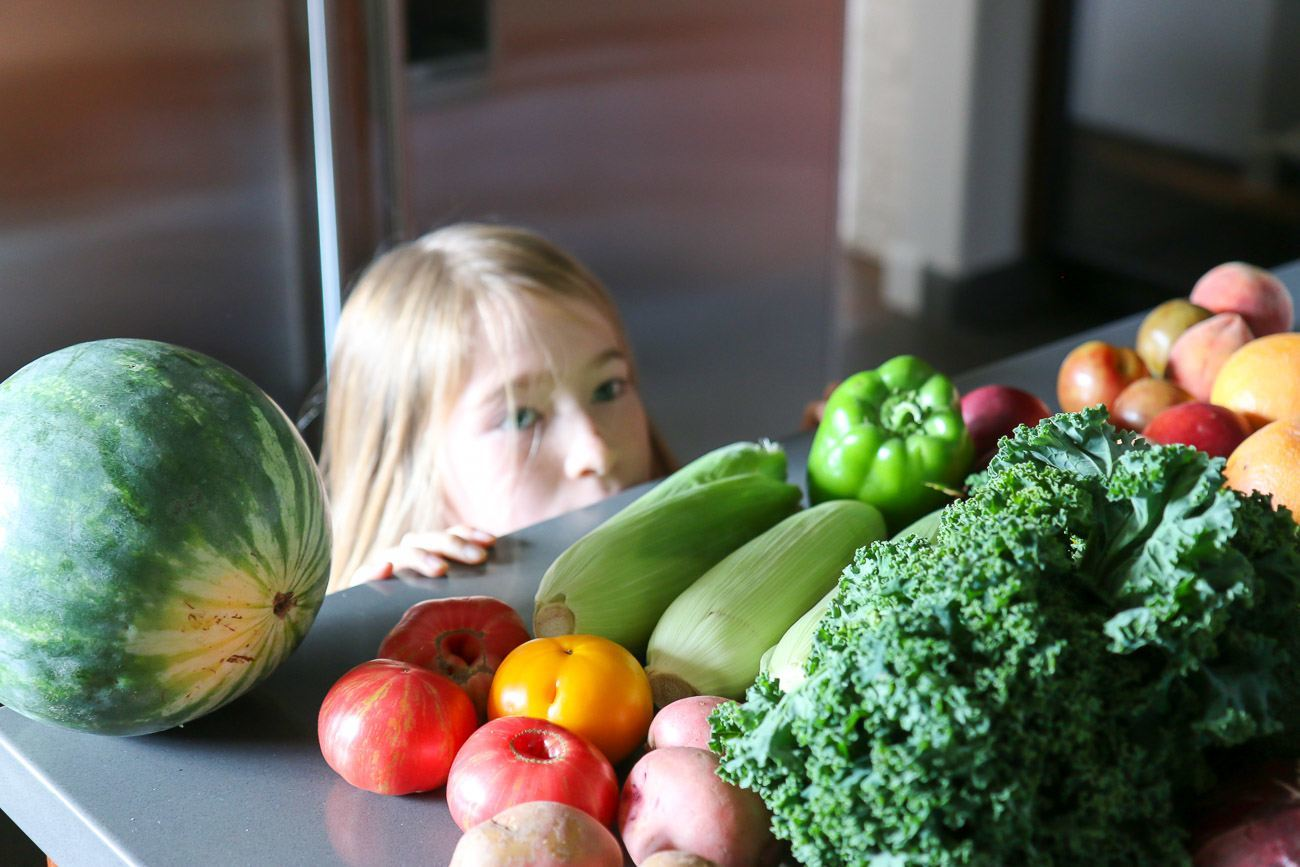 A CSA box with healthy fruit and vegetables as snacks for kids