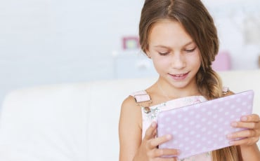 A girl stays connected with grandparents by playing games and reading with them via the HomeTeam App.