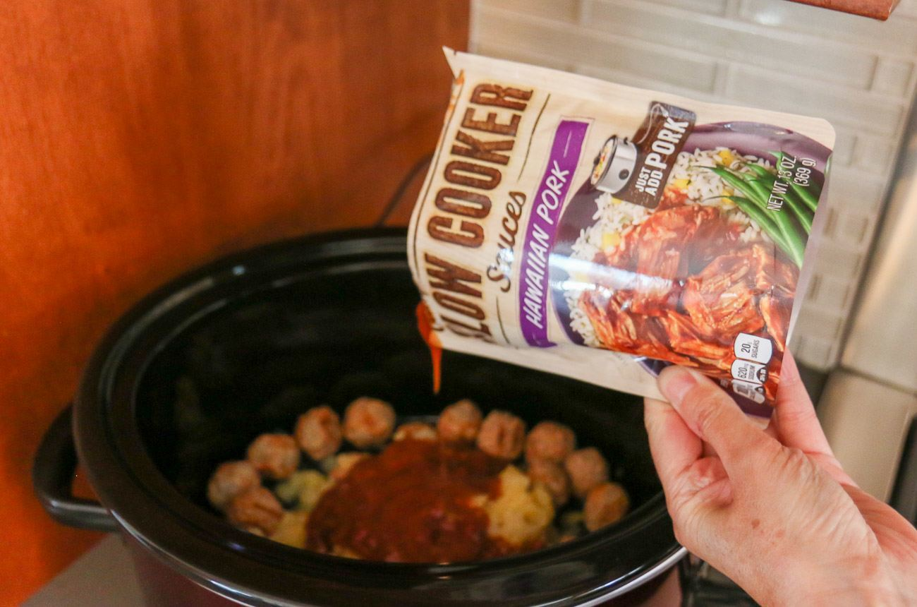 Pouring Campbell's Slow Cooker Sauce on top of meatballs.
