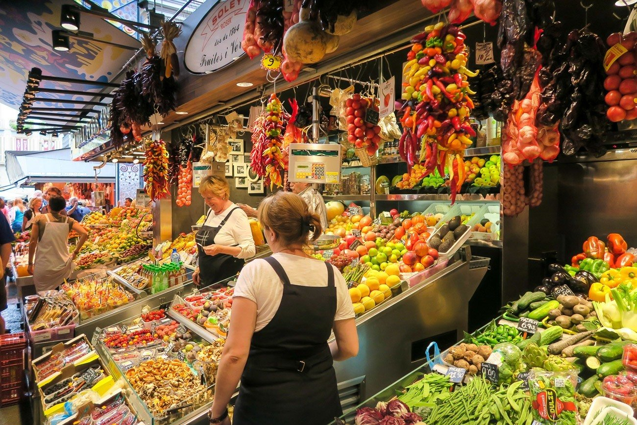 Vendors selling fruit at La Boqueria Market in Barcelona