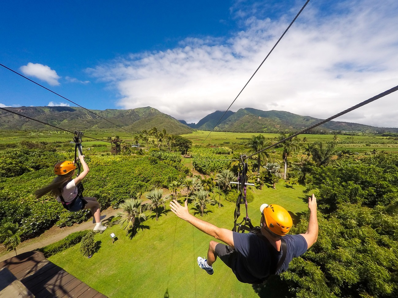 My daughter and husband zip line over a lush plantation with panoramic views at Maui Zipline.