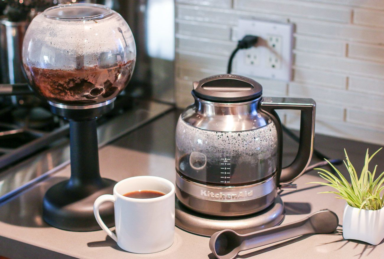 A cup of coffee made in a siphon coffee maker specially-designed for home use.