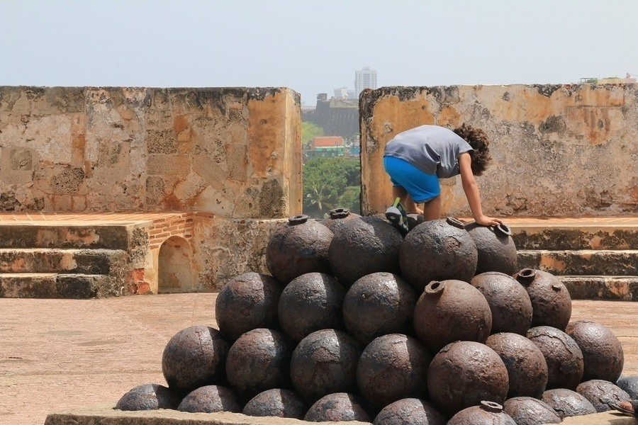 A child climbing on a stack of old cannonballs with Old San Juan in the distance in Fort El Morro, San Juan, Puerto Rico.