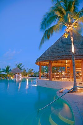 The Palapa Grill and pool at Grand Isle Resort in the Bahamas lit up at night.