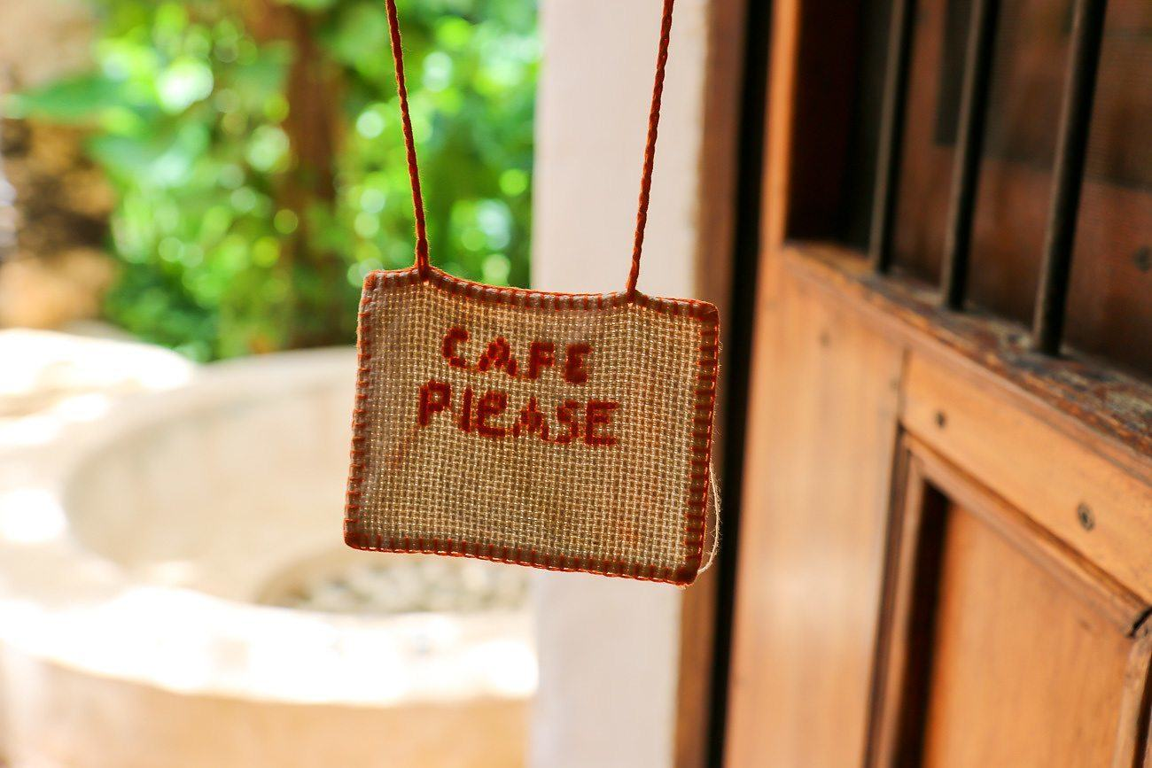 "Guests at Hacienda Petac hang a ""cafe please"" sign on the door when ready for coffee."