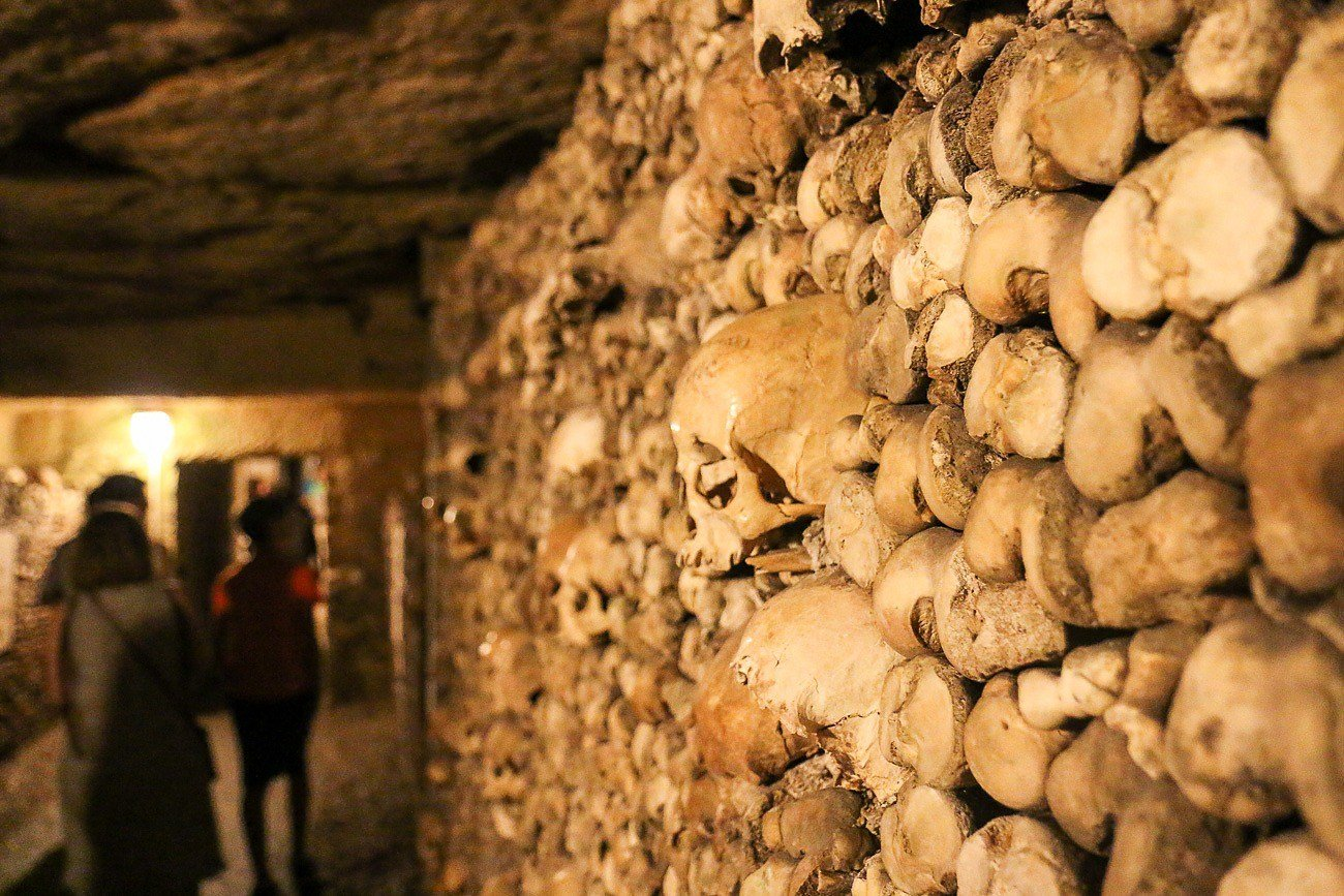 People touring the Paris Catacombs, a popular attraction.