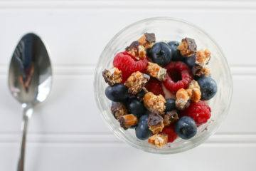 A finished Greek yogurt parfait with fresh fruit and goodnessknows squares.