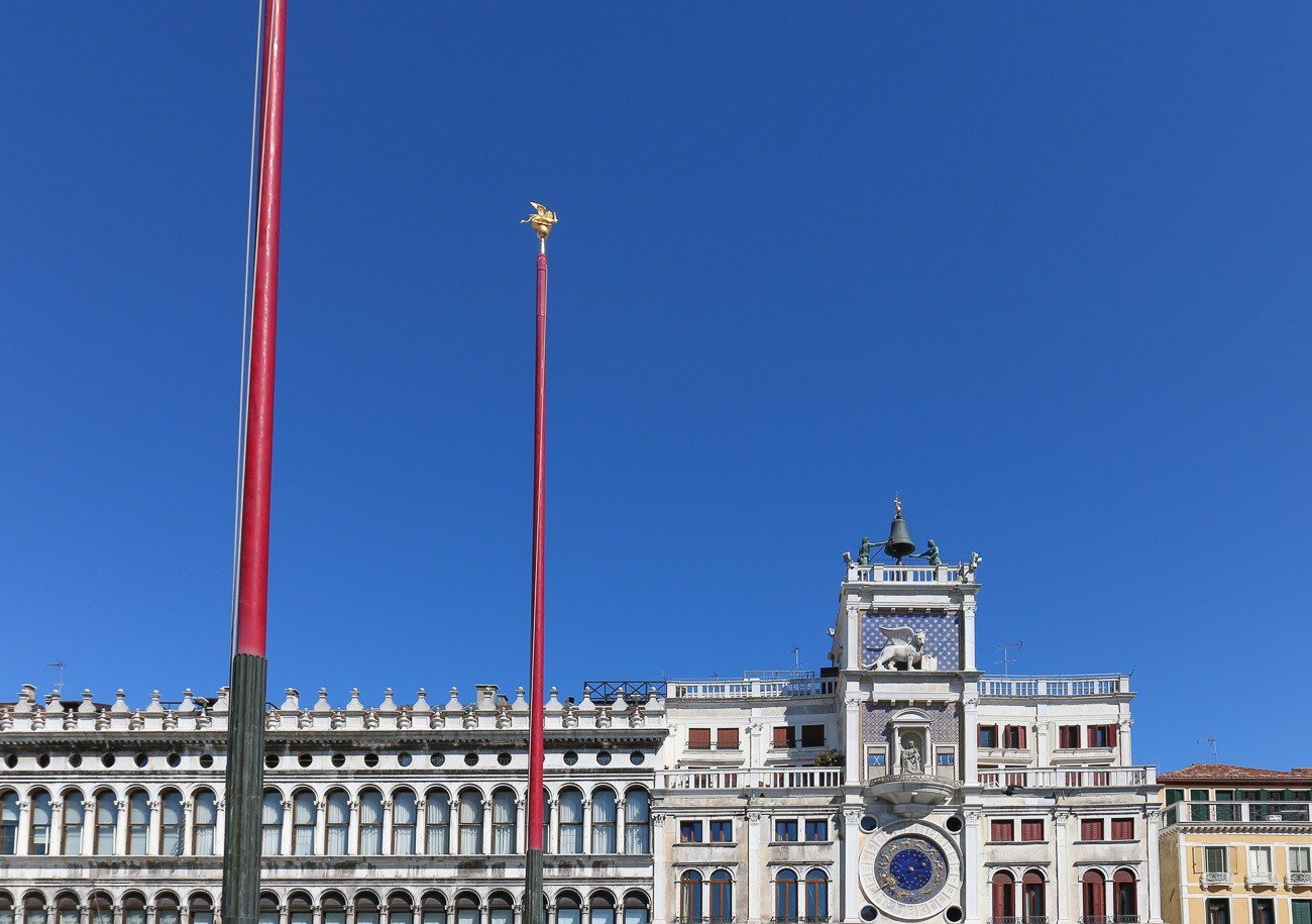 Lions on flag poles and the St. Mark's Clocktower in Venice, Italy.