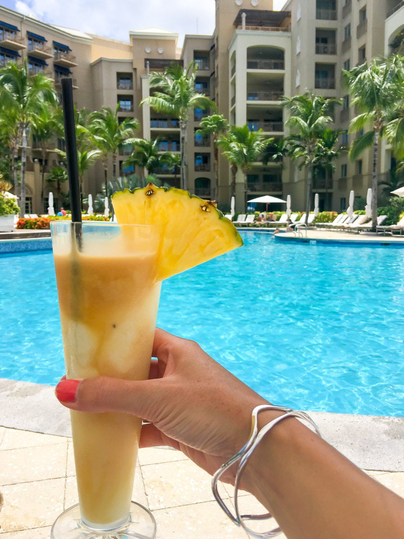 A pina colada at The Ritz-Carlton Grand Cayman paired with bangles from the Lisa Bridge Jewelry Collection