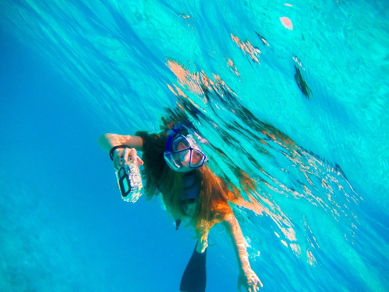 A snorkeler in water with an underwater camera.