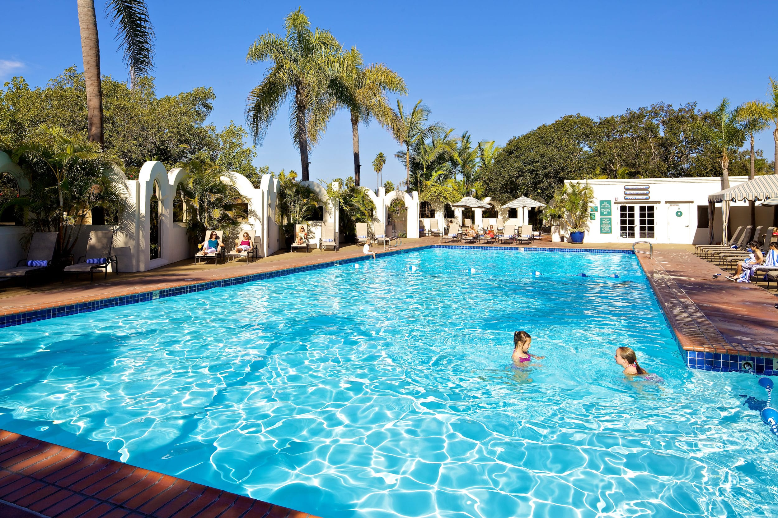 Two kids swim in the Bahia Resort Hotel's outdoor swimming pool on a sunny day.
