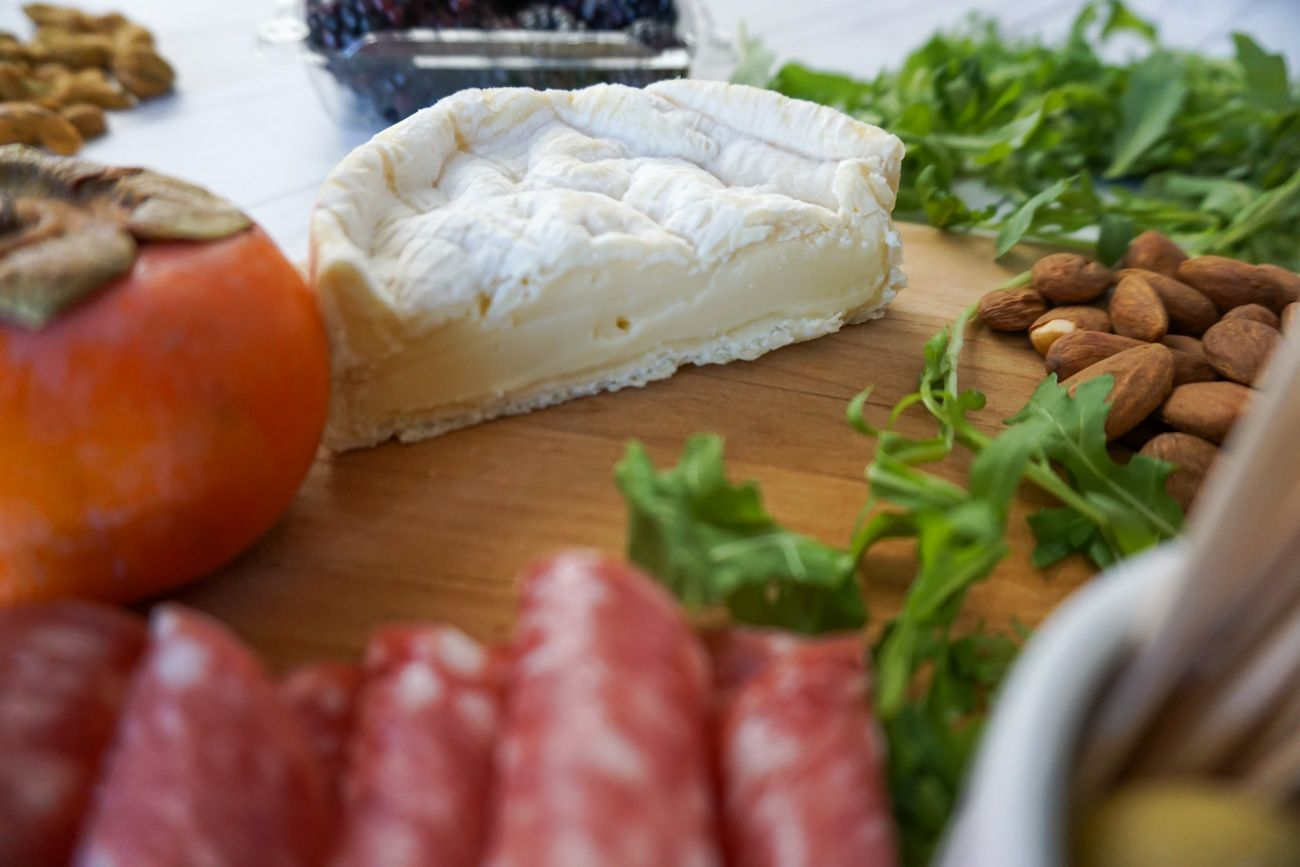 When you make a charcuterie and cheese platter, cut large cheeses in half so guests have easier access to them.