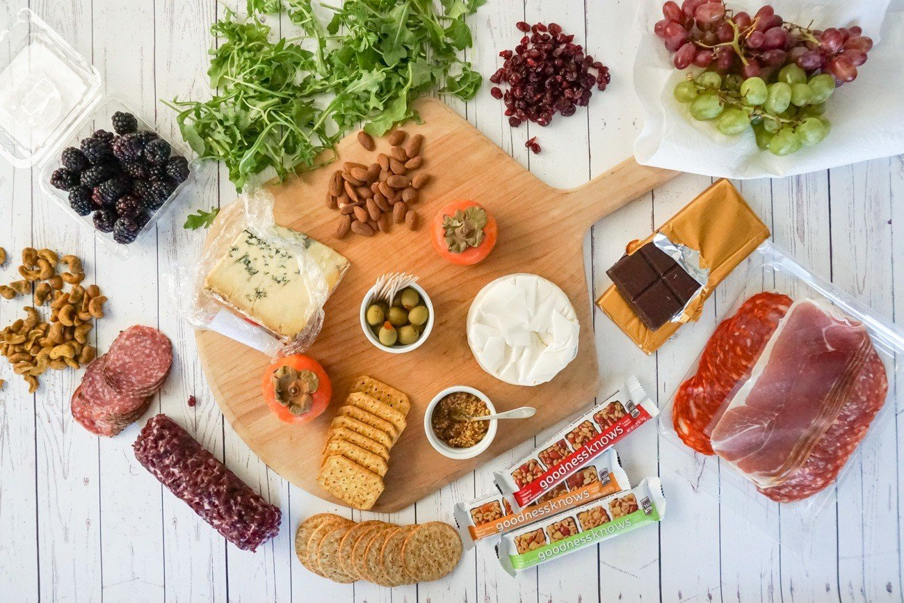 Gather ingredients around a cheese board before placing everything on it.