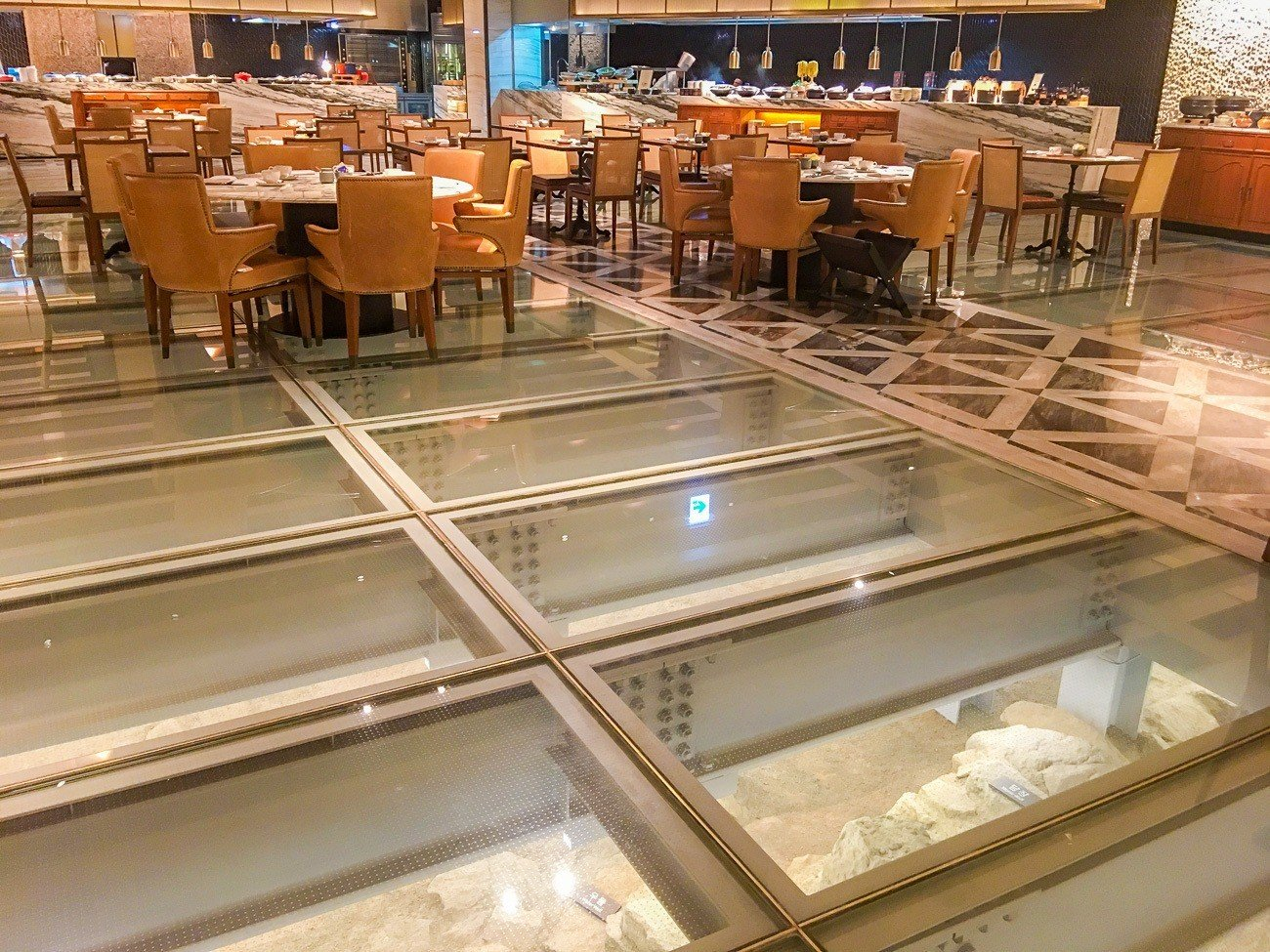 Ruins shown through glass panels in the floor of The Marketplace inside Four Seasons Hotel Seoul.