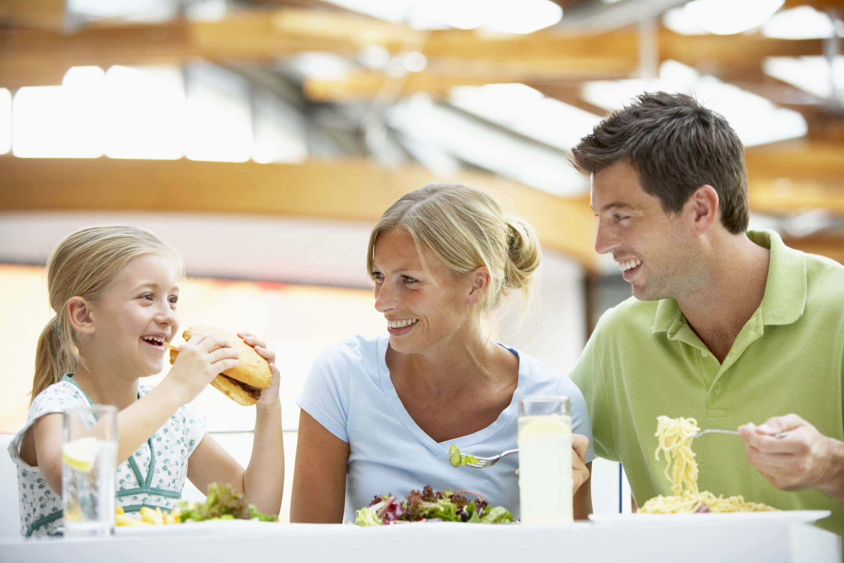 A family of two adults and a little eat lunch together.