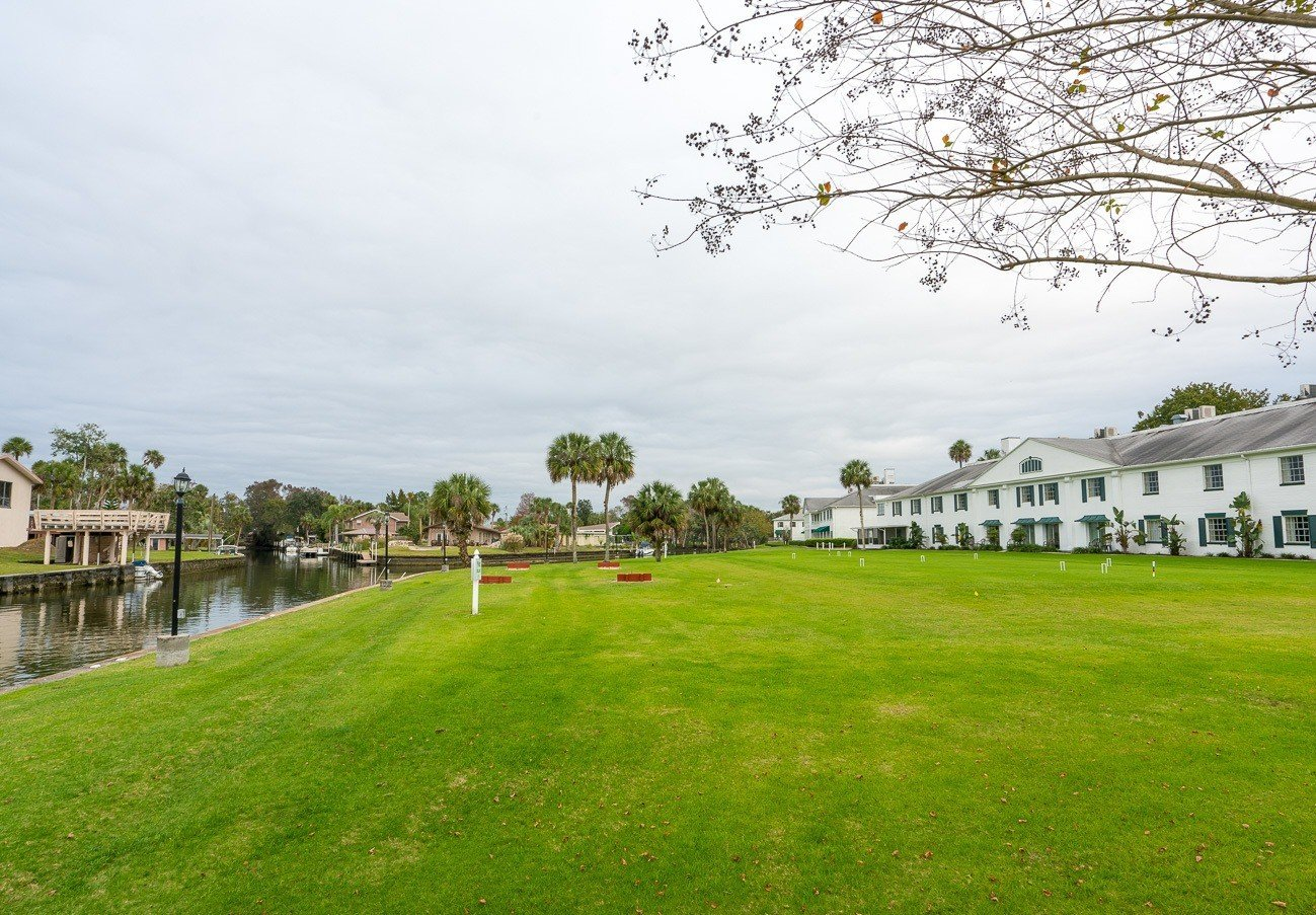 Large  grassy area bordering the river and some guest rooms.