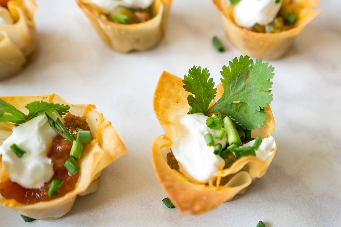 Two-bite taco cups with a cilantro garnish. An easy, tasty party recipe.