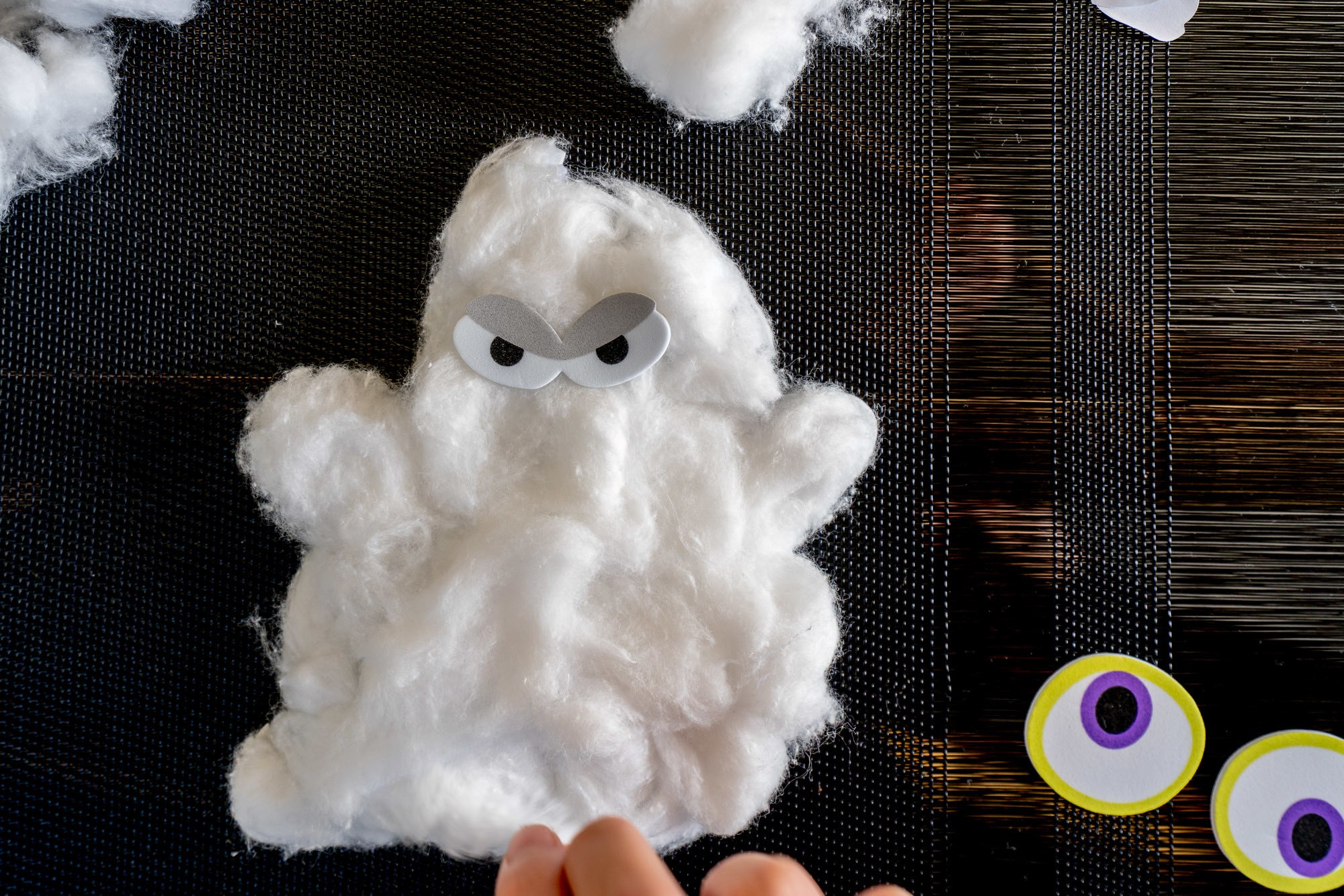 An easy Halloween craft is to make cotton ball ghosts.