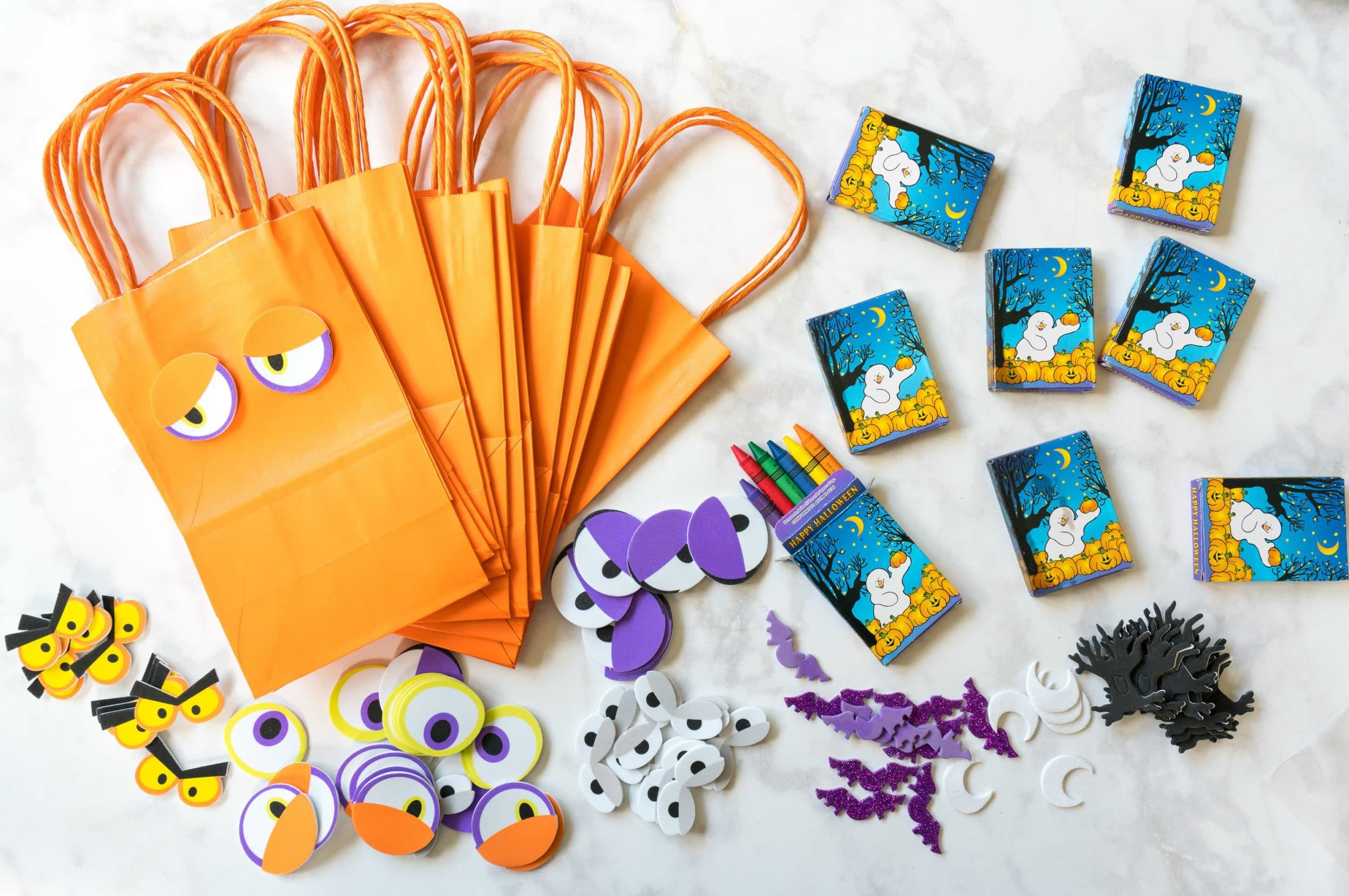 A good activity at a toddler Halloween party is to let them decorate their own favor bags.