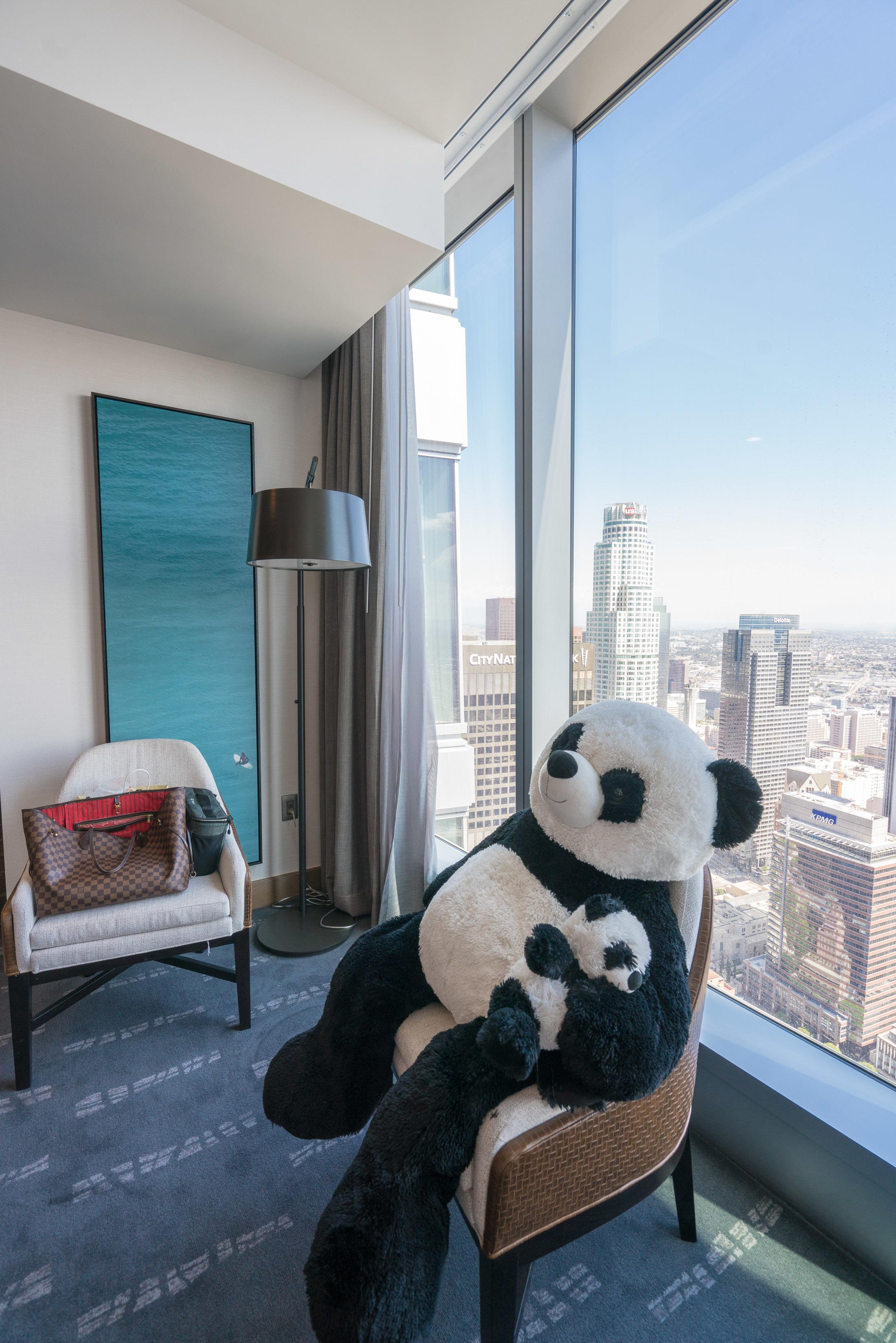 Giant panda sitting in a chair with a view of downtown Los Angeles behind it.