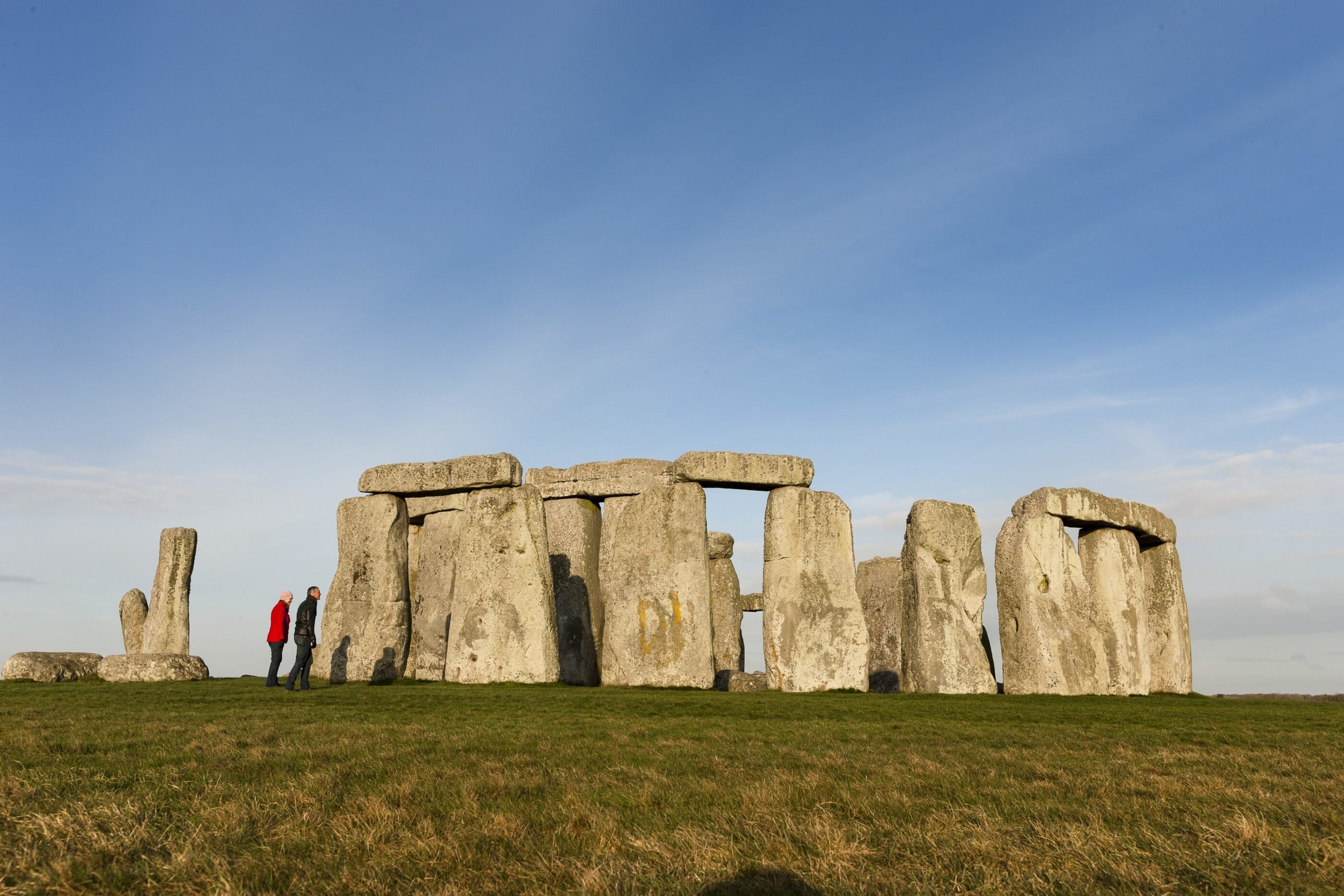 People stand at the perimeter of Stonehenge, one of the best day trips from London.