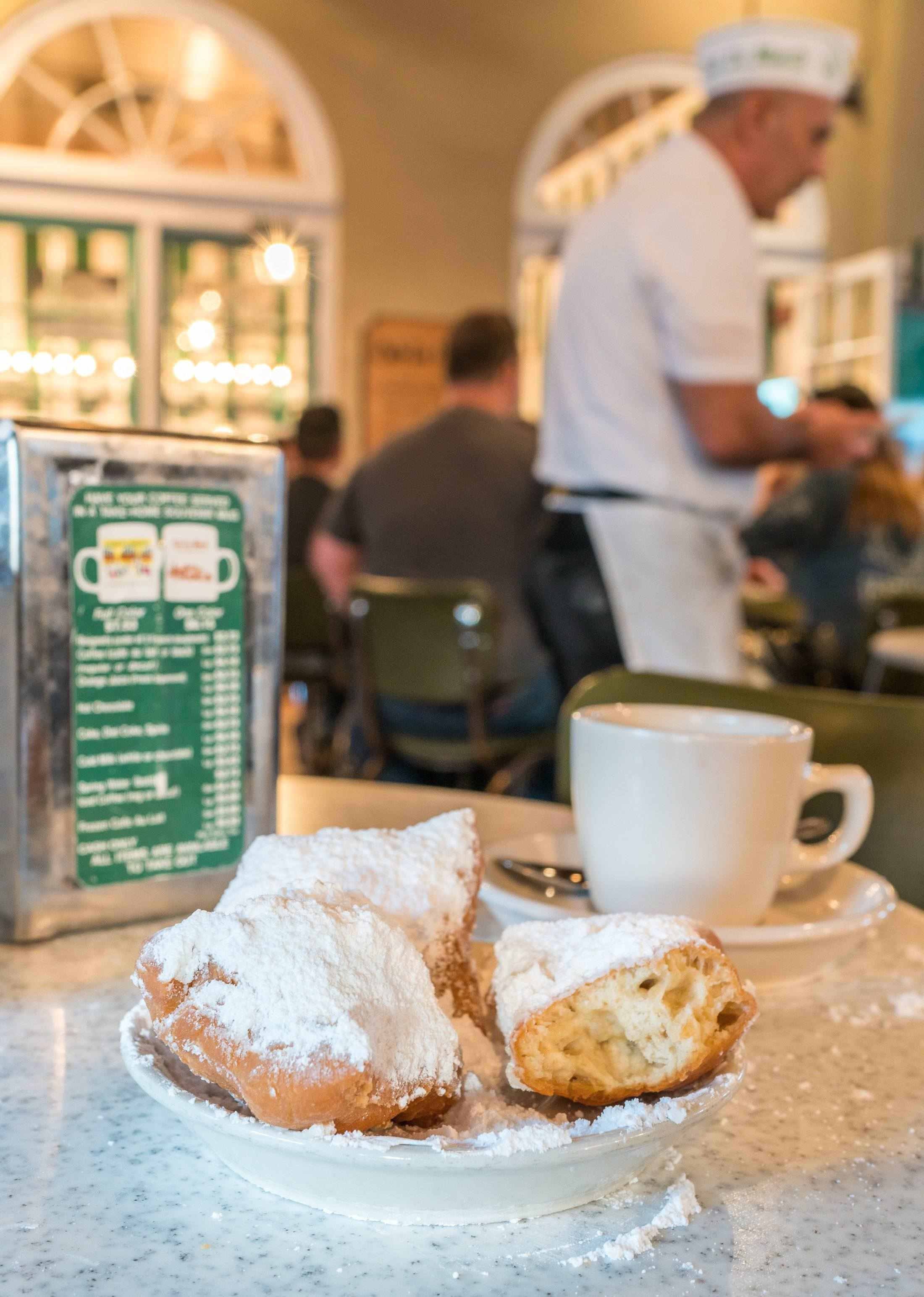Beignets at Cafe du Monde are must-eat New Orleans foods.