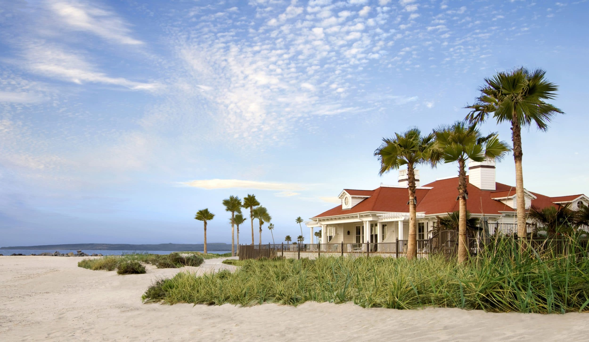 Best beach hotels in San Diego: Beach Village at The Del buildings are separated from the beach by a boardwalk.