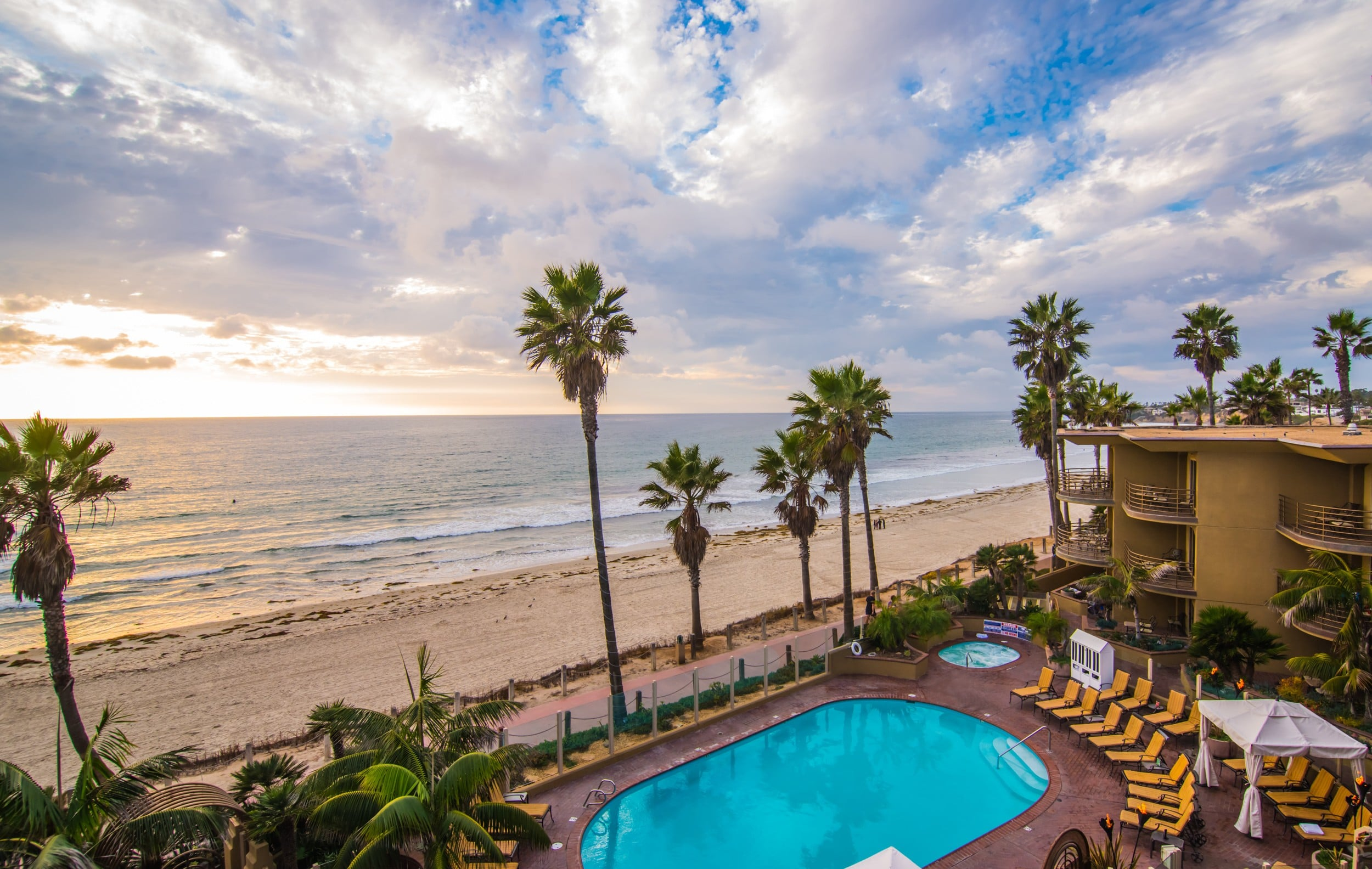 Aerial view over the pool to the beach at Pacific Terrace Inn, one of the best San Diego hotels on the beach.