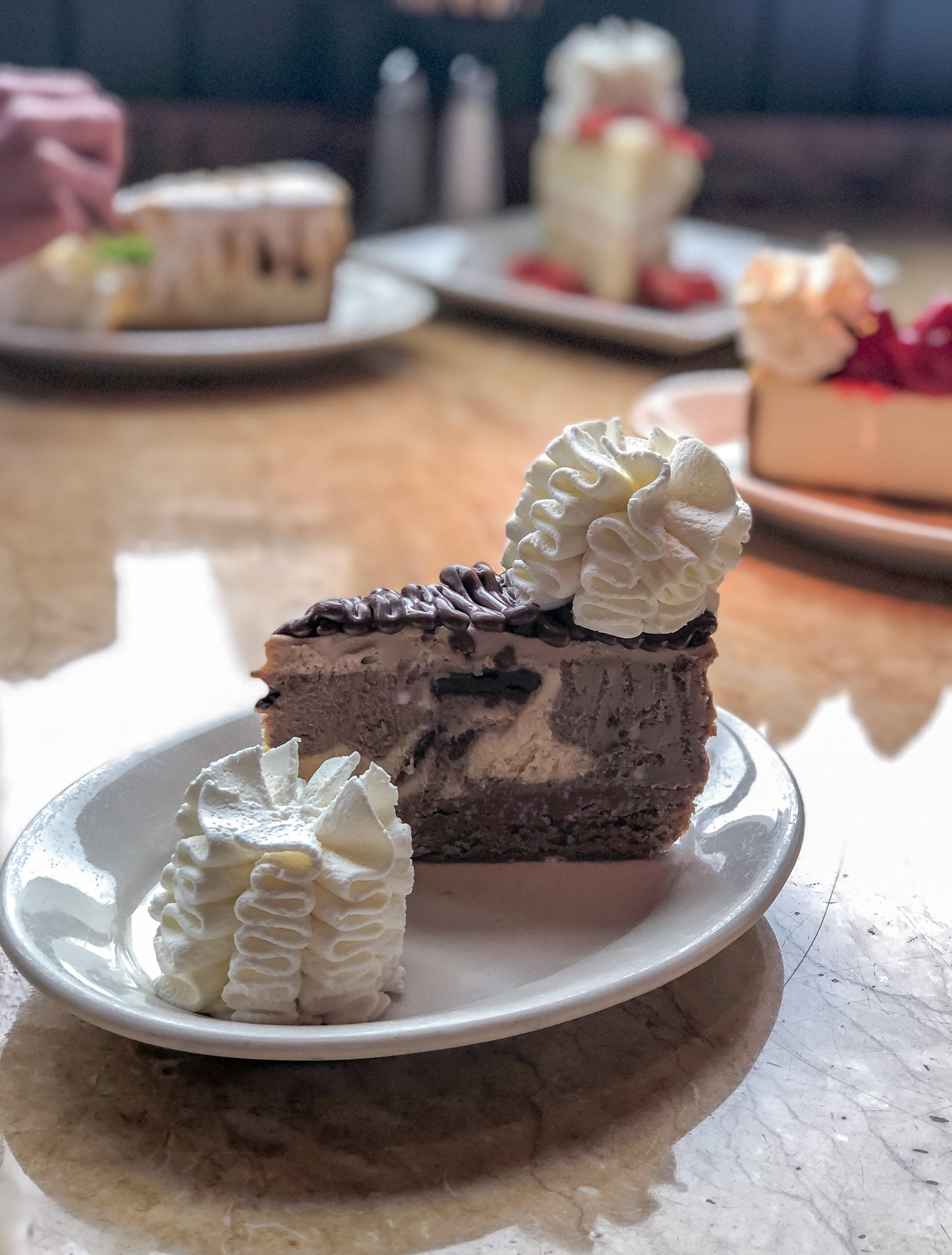 A slice of Chocolate Hazelnut Crunch Cheesecake with whipped cream on top.