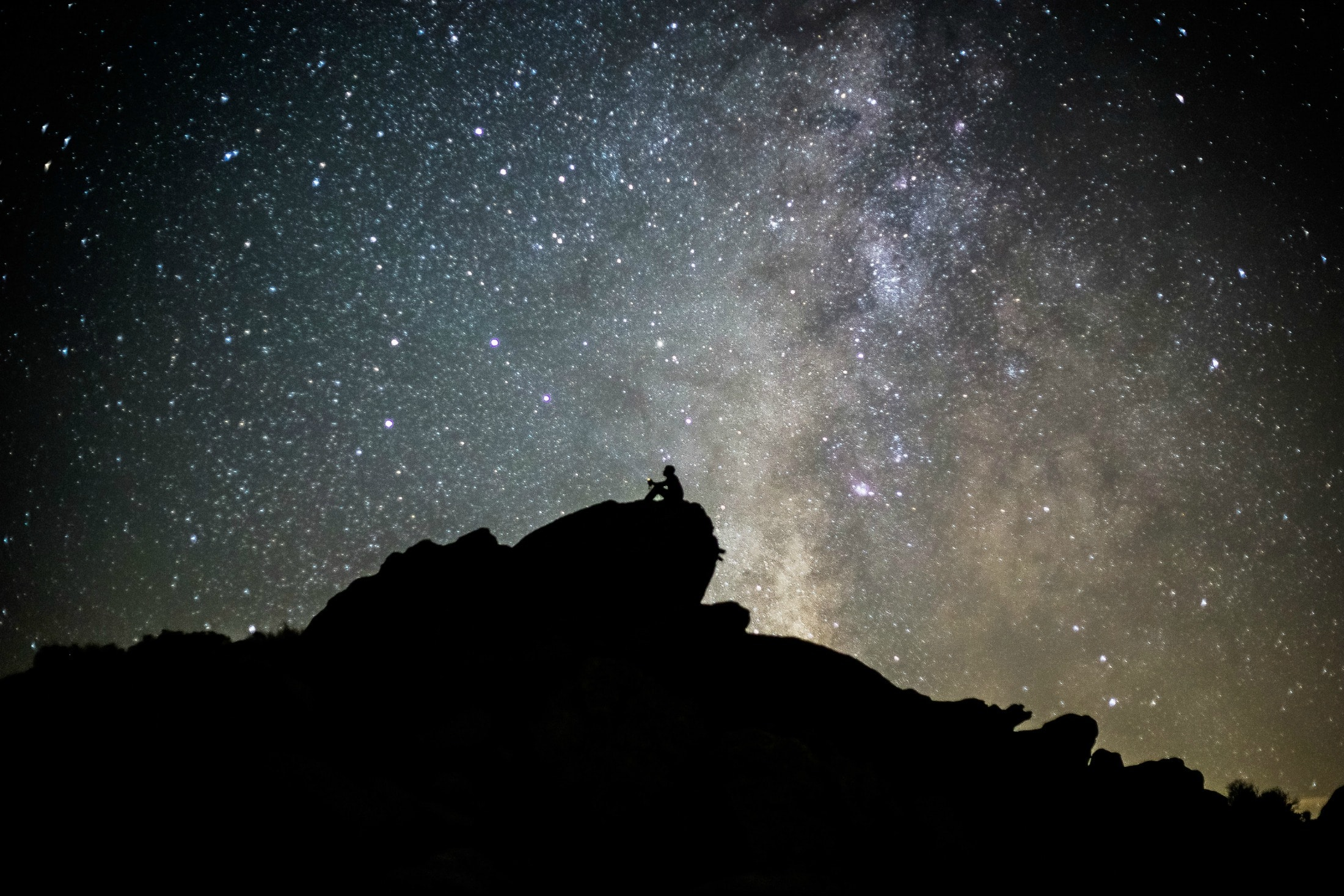 A man sits on a rock under stars — stargazing is one of the very popular things to do at Anza-Borrego Desert State Park