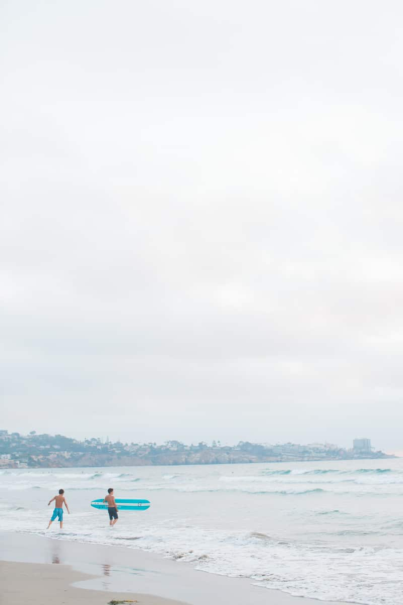 Surfers at La Jolla Shores Beach captured by a Flytographer vacation photographer.