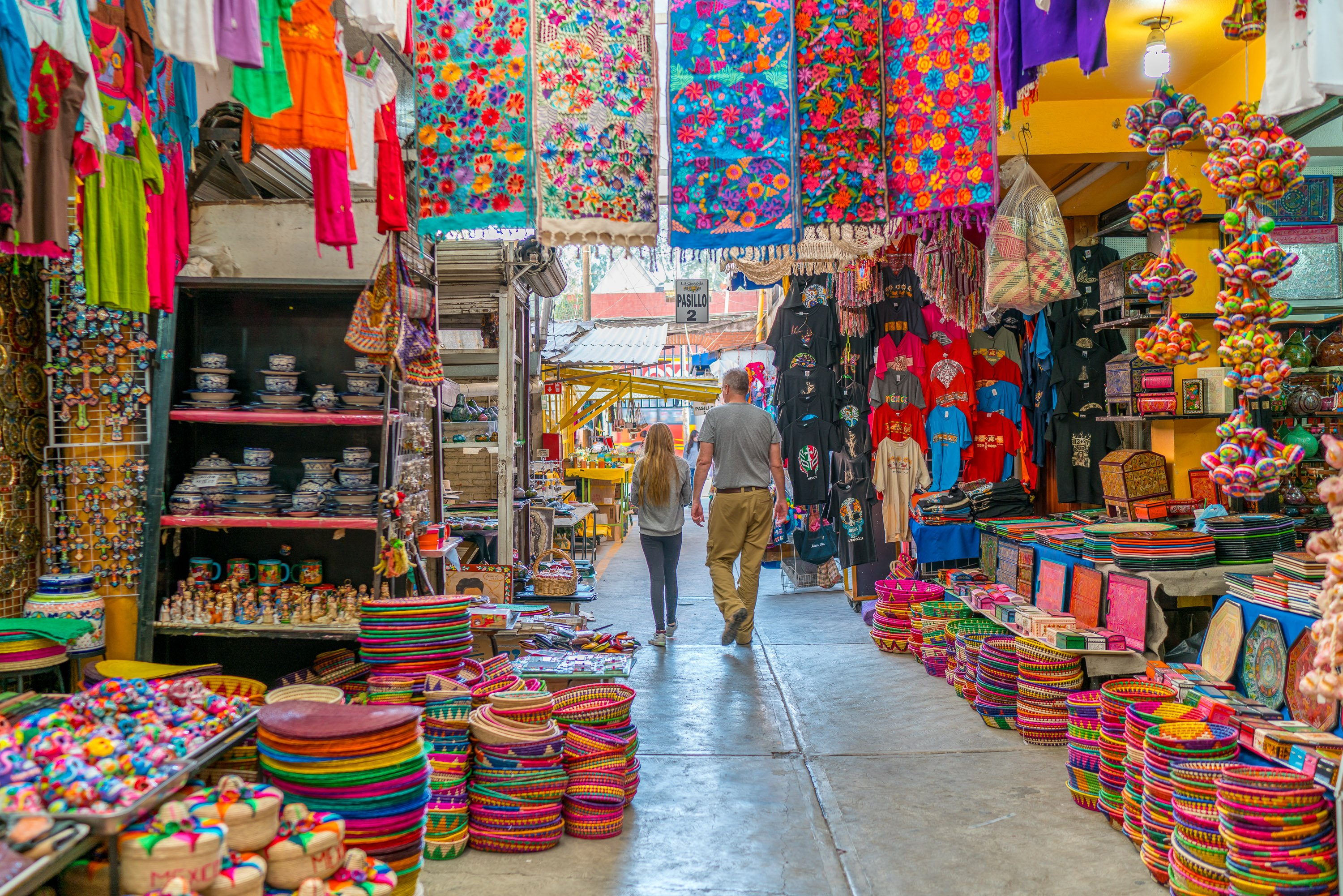 Brightly-colored blankets, hats, and ceramics line an aisle inside of La Ciudadela market in Mexico City.