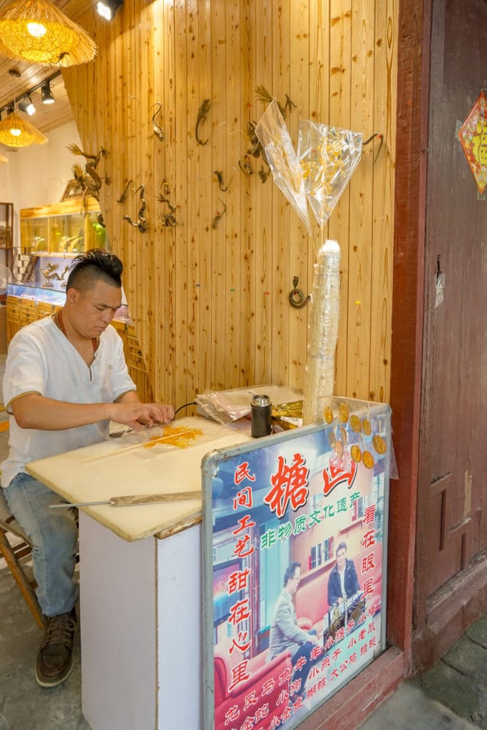 A man sits at a desk and paints animals with sugar to sell on a stick.