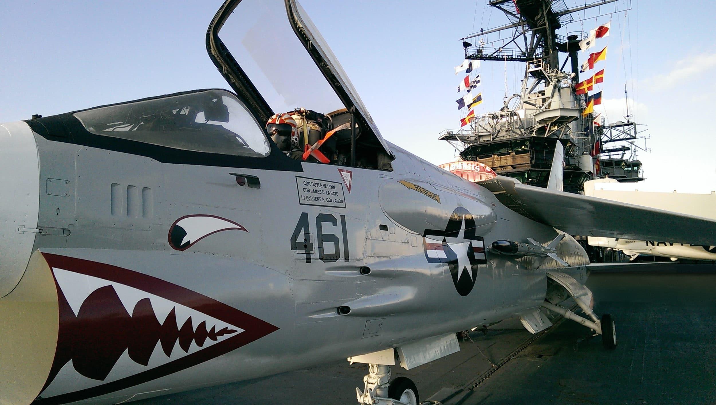 Un avion militaire avec un cockpit ouvert se trouve sur le pont du USS Midway Museum.