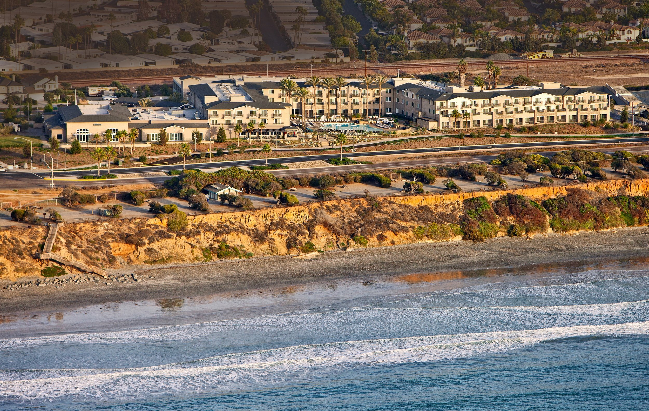 Aerial view of the ocean and entire Cape Rey Carlsbad, a Hilton Resort.