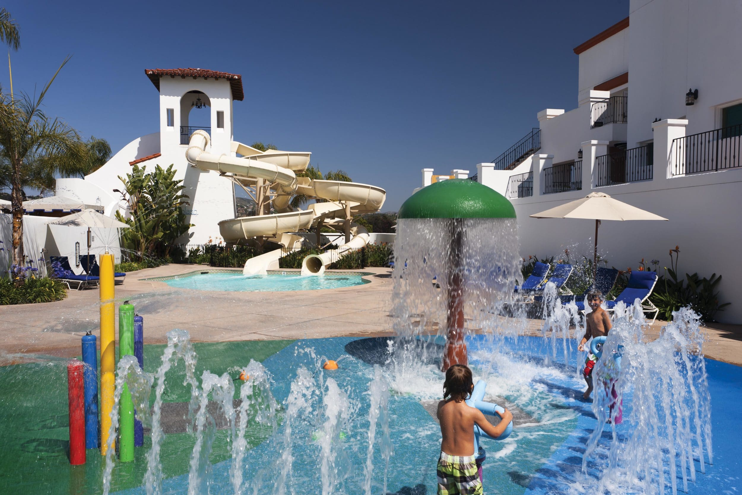 Kids play on the splash pad at Omni La Costa Resort with the water slide in the background.