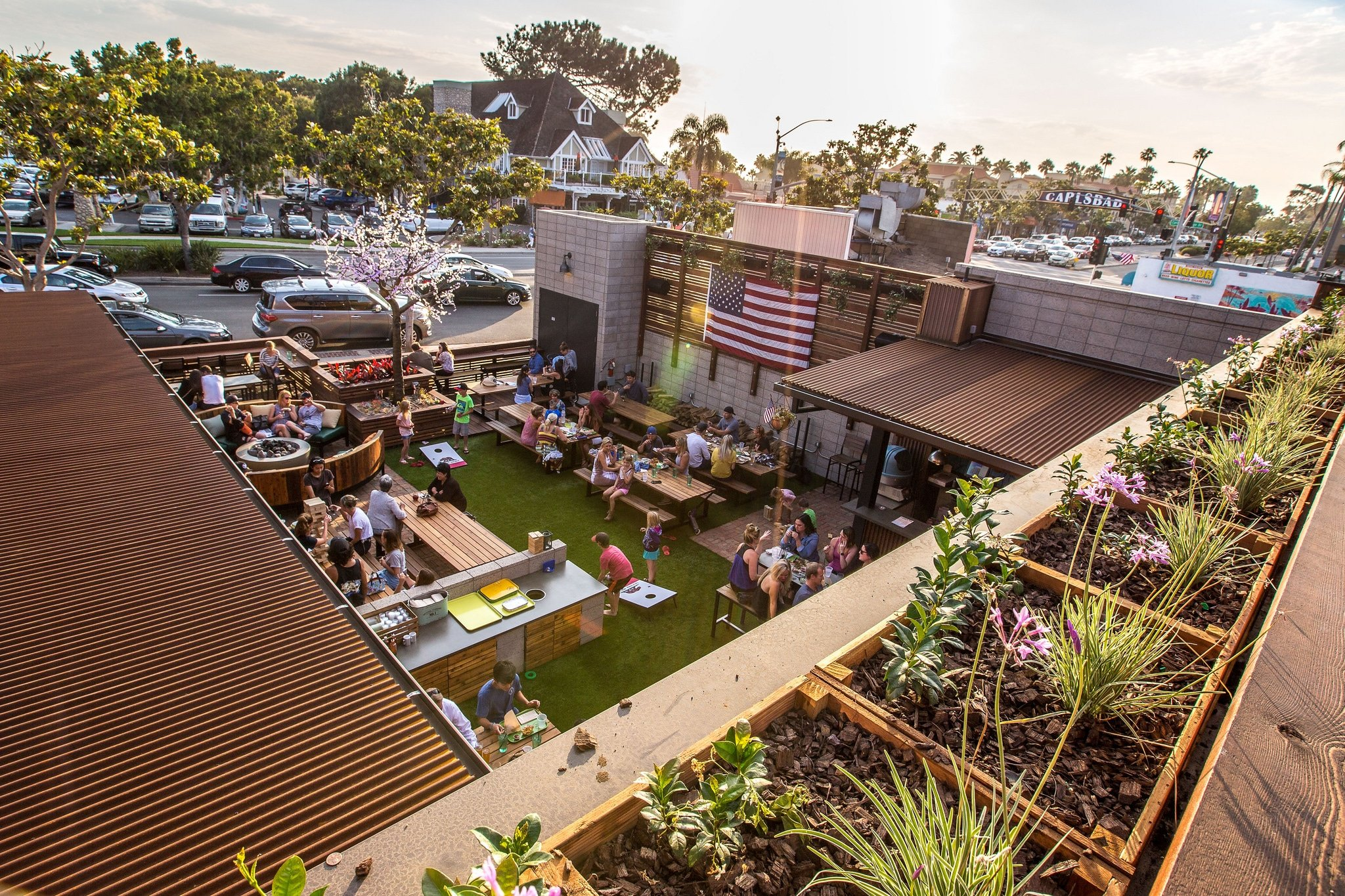 Kids play corn hole while guests hang out at picnic tables at Park 101 in Carlsbad's Garden Pub area.