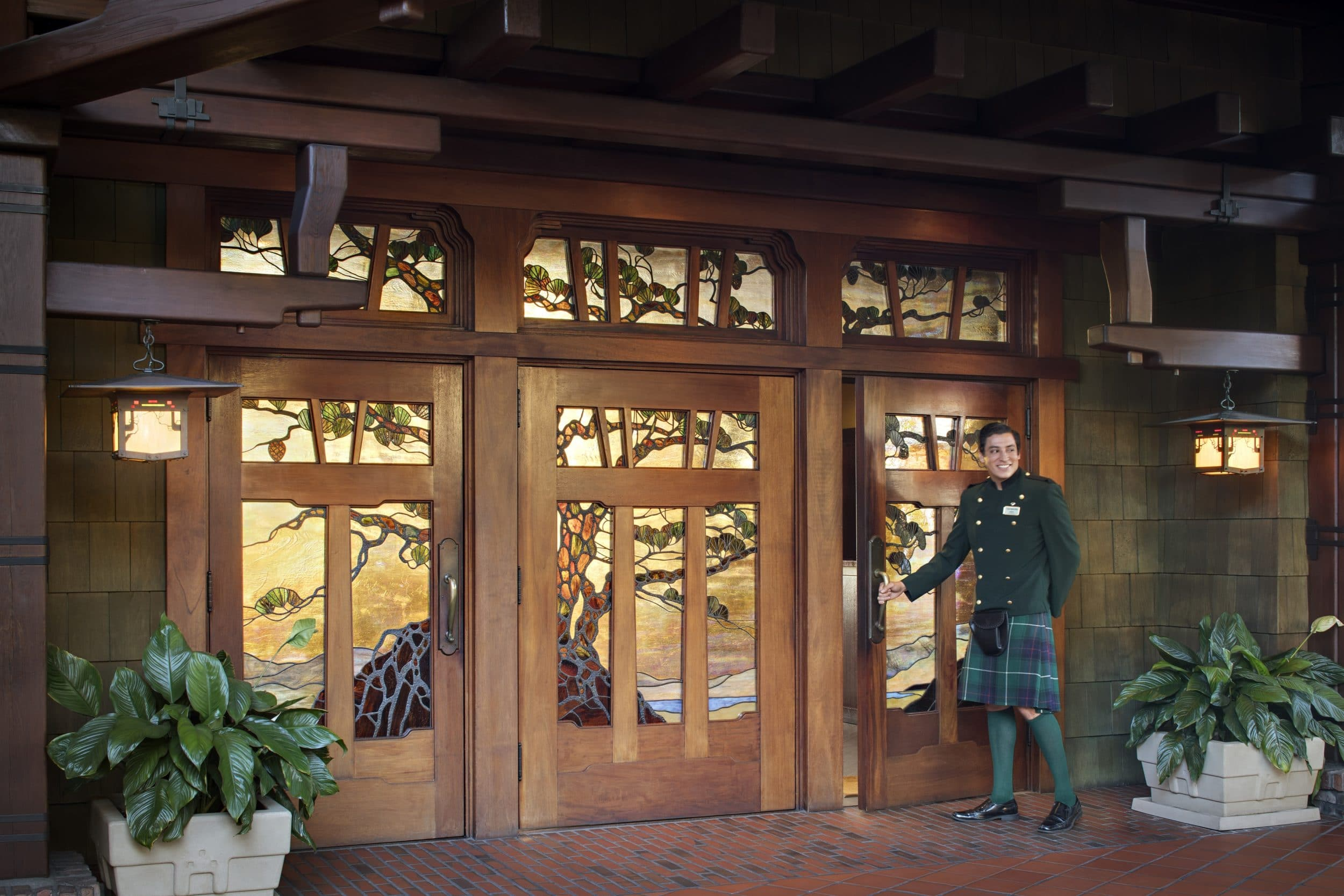A kilted doorman opens the stained glass door to the lobby at The Lodge at Torrey Pines