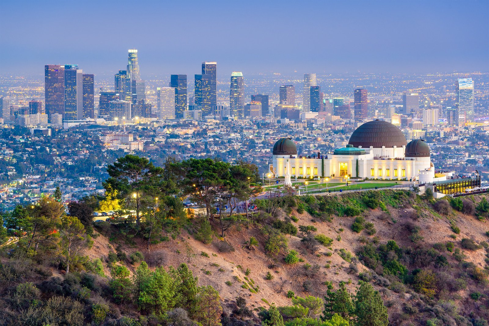 Aerial view of Griffith Park Observatory with city skyline in the background.