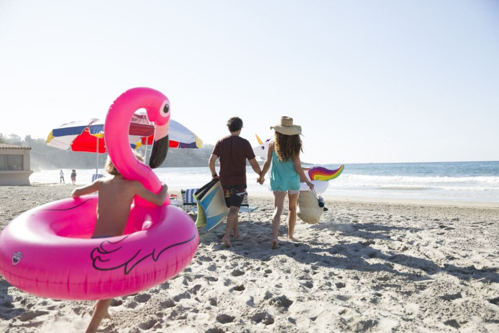 A child runs with an inflatable flamingo around him behind parents carrying beach gear on the beach.