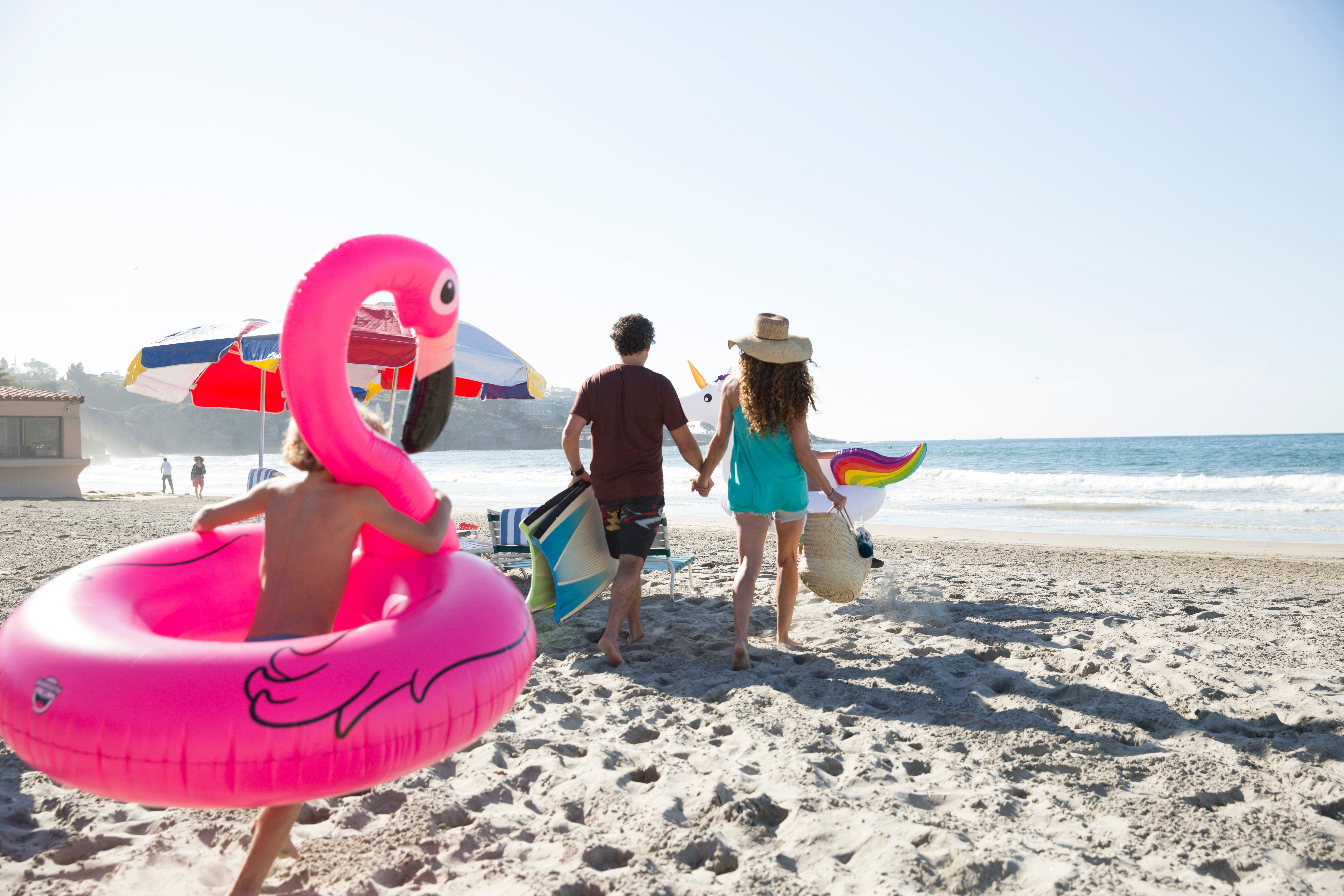 A child runs with an inflatable flamingo around him behind parents carrying beach gear on La Jolla Shores beach.