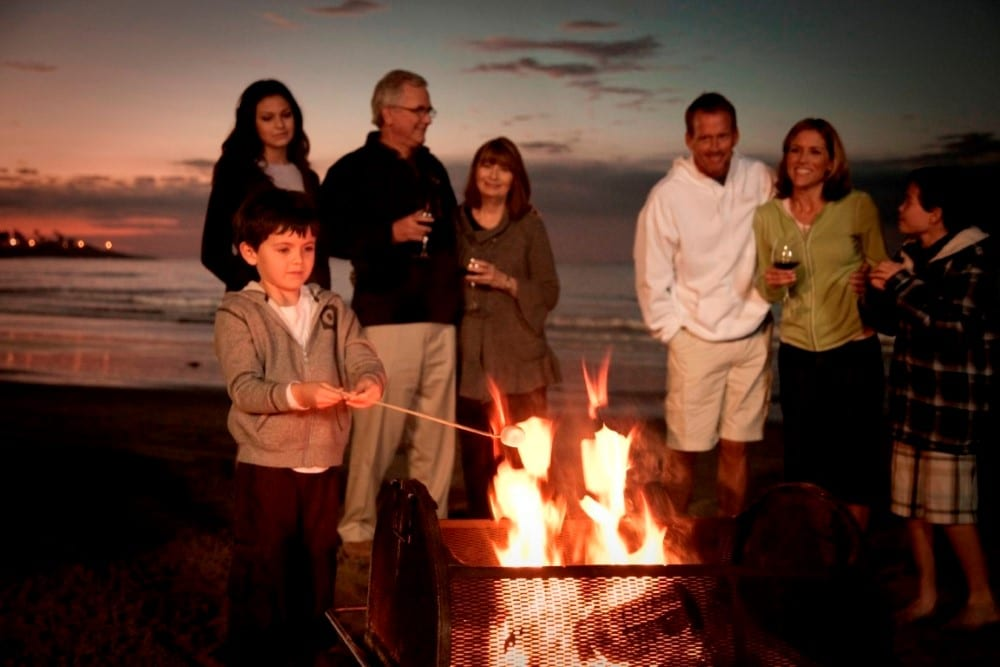 A family roasting s'mores at night on the beach at La Jolla Beach and Tennis Club