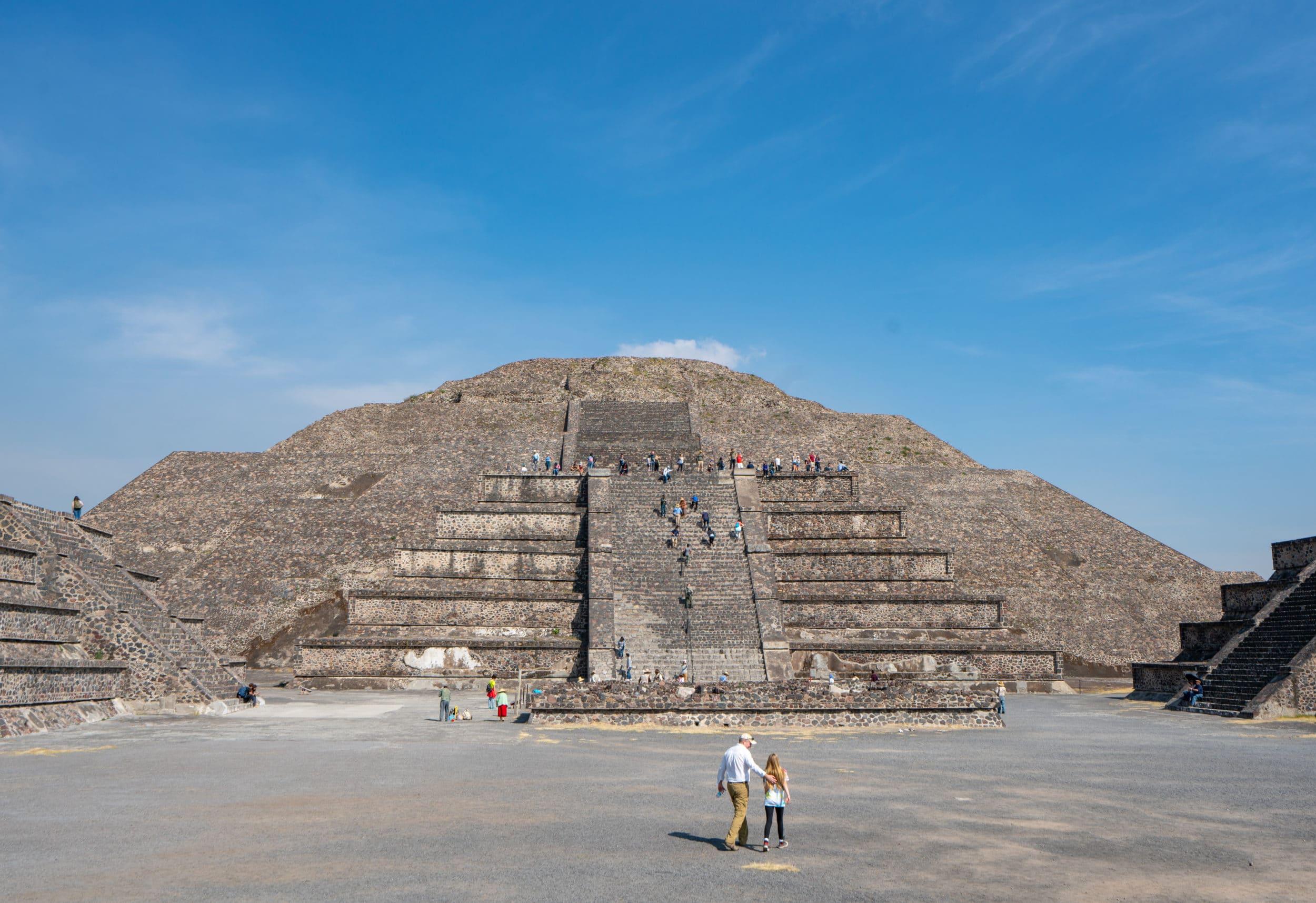 My daughter and husband walk toward a pyramid at Teotihuacan on a sunny day.