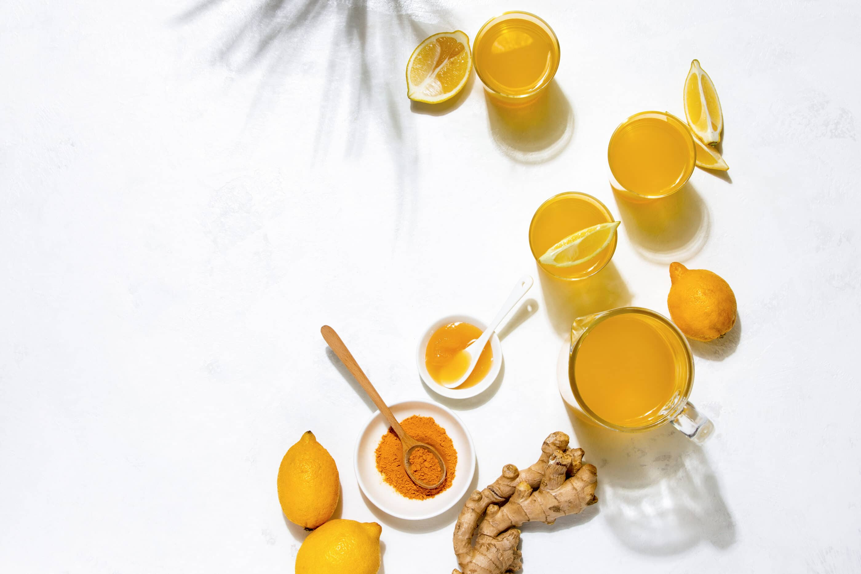 Turmeric and lemon water in cups on a white table with ginger.