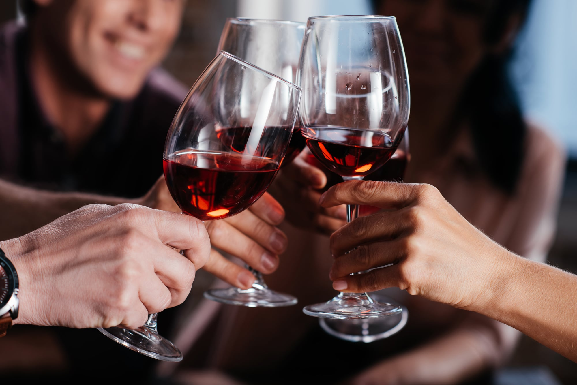 A group saying cheers with red wine in wine glasses.